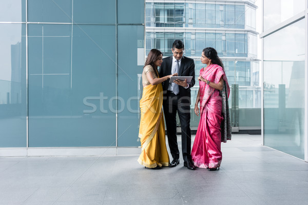 Three Indian business people using a tablet PC indoors Stock photo © Kzenon