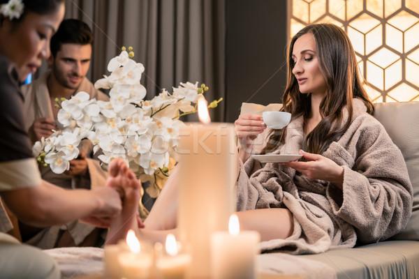 Stock photo: Beautiful woman drinking tea during therapeutic foot massage