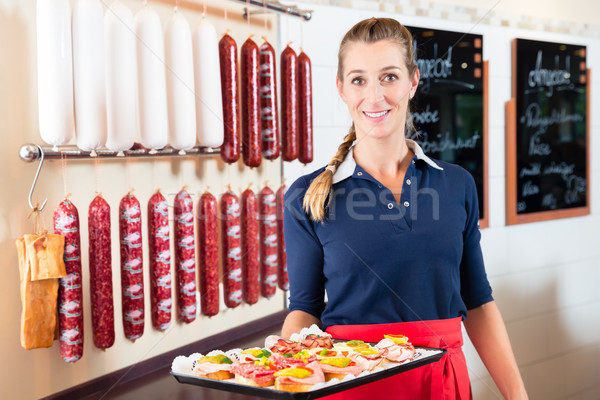 Woman offering finger food and little bites in meat shop Stock photo © Kzenon