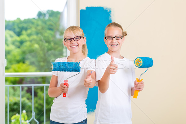 Girls painting a wall in the family home Stock photo © Kzenon