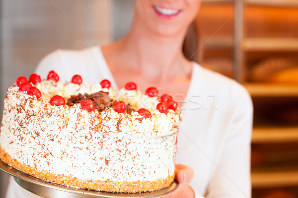 Female baker or pastry chef with torte Stock photo © Kzenon