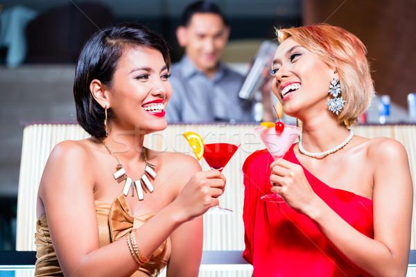 Asian women drinking cocktails in fancy bar Stock photo © Kzenon