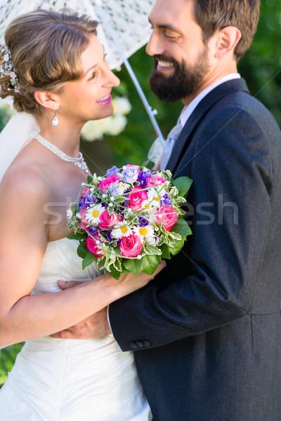 Bridal couple embracing each other in summer garden Stock photo © Kzenon