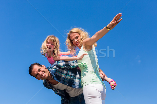 Father, mother and daughter playing plane Stock photo © Kzenon