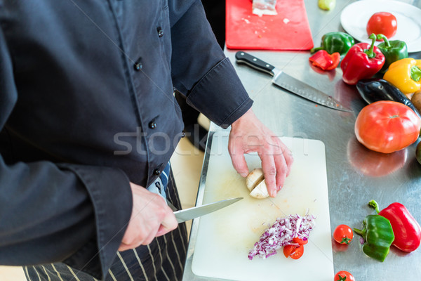 Chef in restaurant kitchen cutting onions Stock photo © Kzenon