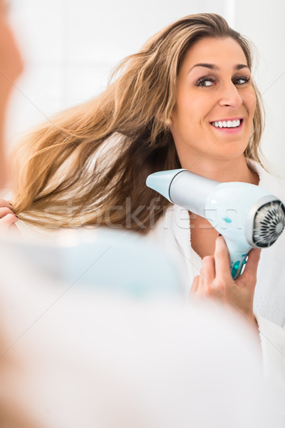 Woman blow drying her hair in front of mirror Stock photo © Kzenon