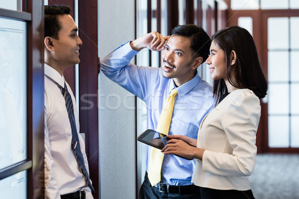 Co-workers in office hallway talk about project Stock photo © Kzenon