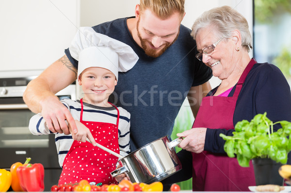 Stock photo: Mom, dad, granny and grandson together in kitchen preparing food