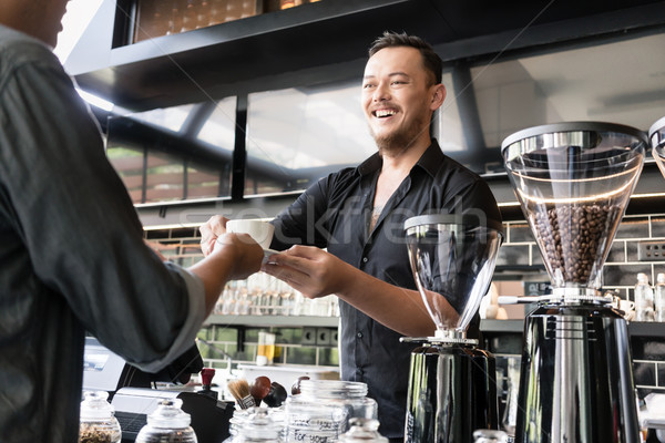 Friendly bartender serving espresso coffee to a customer in a mo Stock photo © Kzenon
