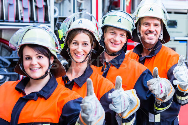 Stock photo: Four fire fighters doing thumbs up