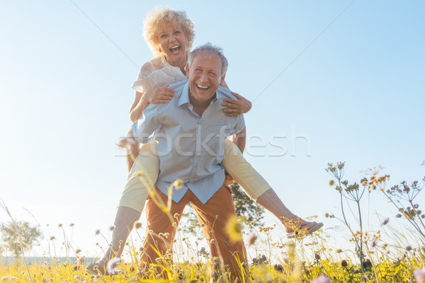 Happy senior man laughing while carrying his partner on his back Stock photo © Kzenon