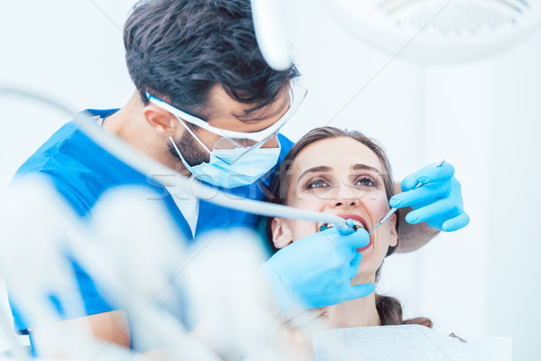 Young woman during painless oral treatment in the modern dental clinic Stock photo © Kzenon
