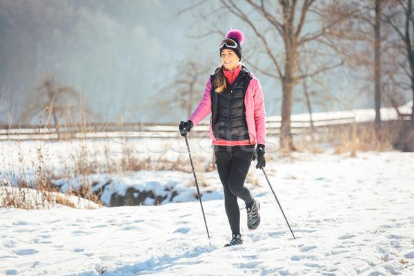 Fit woman Nordic walking in winter landscape Stock photo © Kzenon