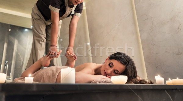 Young woman enjoying the stretching techniques of Thai massage Stock photo © Kzenon