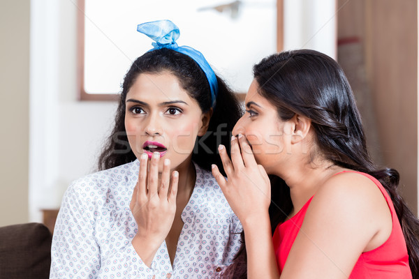 Young woman whispering to her best friend gossips Stock photo © Kzenon