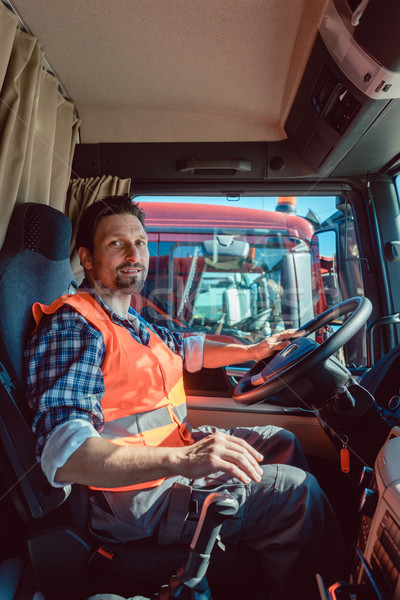 Lorry or truck driver sitting in the cabin of his vehicle Stock photo © Kzenon