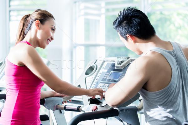 Coach supervising young Asian woman on treadmill  Stock photo © Kzenon