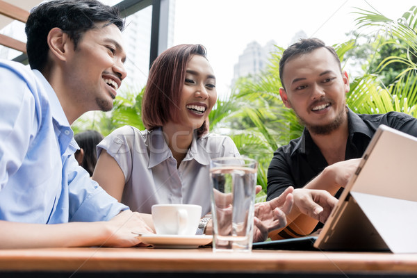 Three young Asian friends smiling while using together a tablet  Stock photo © Kzenon
