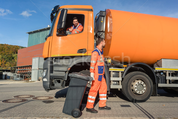 Two garbagemen working together on emptying dustbins  Stock photo © Kzenon