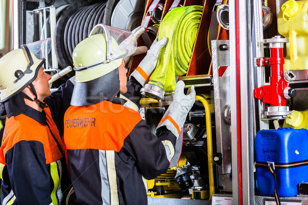Stock photo: Fire fighters loading hoses into operations vehicle
