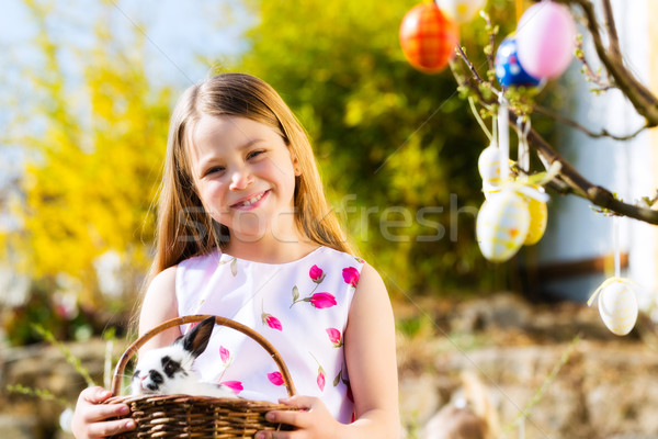 Child on Easter egg hunt with bunny Stock photo © Kzenon