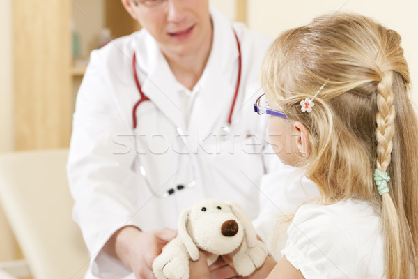 Child giving a soft toy to doctor Stock photo © Kzenon