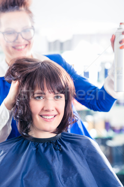 Hairdresser styling woman hair in shop Stock photo © Kzenon