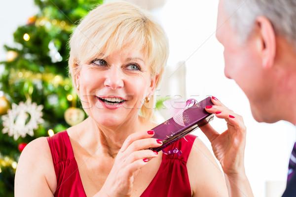 Senior woman is curious about Christmas gift Stock photo © Kzenon