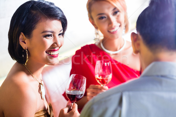 Asian friends drinking wine in fancy bar Stock photo © Kzenon