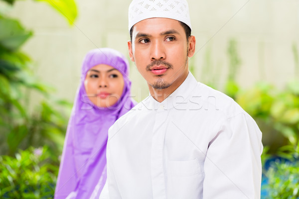 Asian Muslim couple, man and woman, praying at home Stock photo © Kzenon