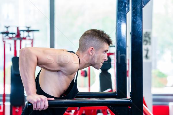Man training dips in fitness center or gym Stock photo © Kzenon