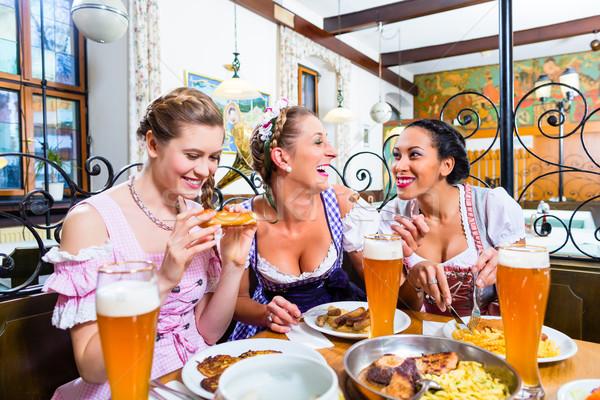 Women in Bavarian restaurant eating food Stock photo © Kzenon