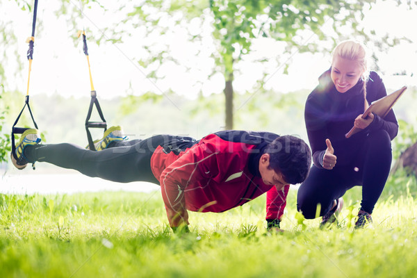 Sport couple outdoors with sling trainer Stock photo © Kzenon