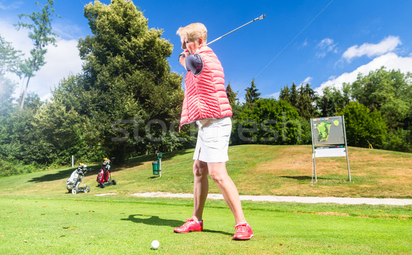 Senior woman doing tee stroke on golf course Stock photo © Kzenon