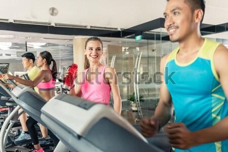 sportive man on treadmill flirting with smiling girls Stock photo © Kzenon