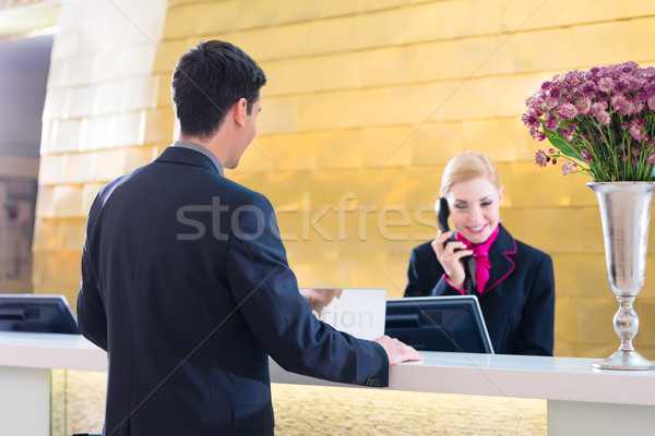 Hotel receptionist with phone and guest Stock photo © Kzenon
