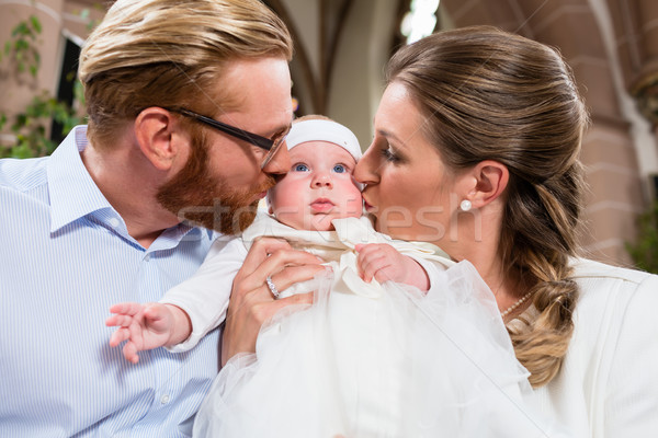 Young parents kiss their baby at the same time after the christe Stock photo © Kzenon