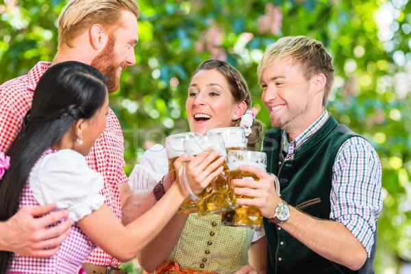 Friends in beer garden clinking glasses with beer Stock photo © Kzenon