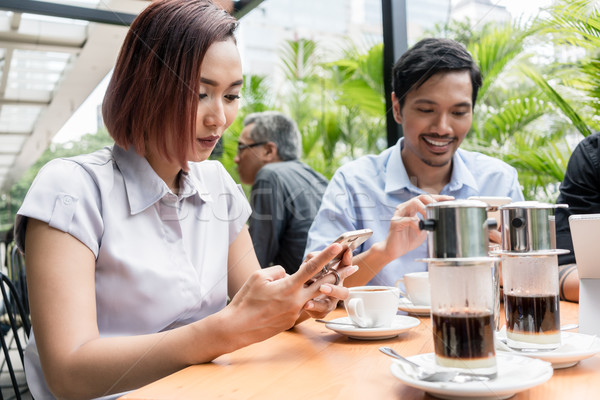 Three friends using devices connected to the wireless internet n Stock photo © Kzenon