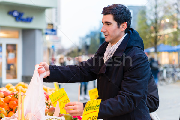 Man buying groceries on farmers market stand Stock photo © Kzenon