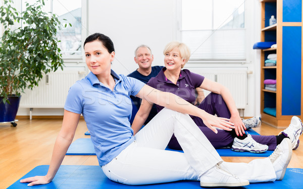 Physio showing back exercises to her patients Stock photo © Kzenon