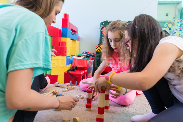 girls playing together with wooden toy blocks on the floor durin Stock photo © Kzenon