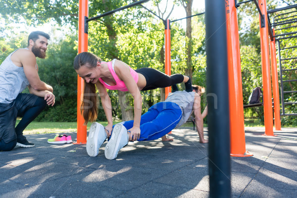 Young woman and her workout partner doing couple push-up exercise Stock photo © Kzenon