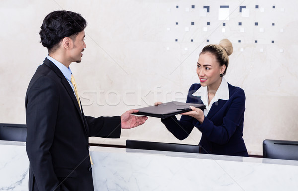 Applicant giving his documents to receptionist Stock photo © Kzenon