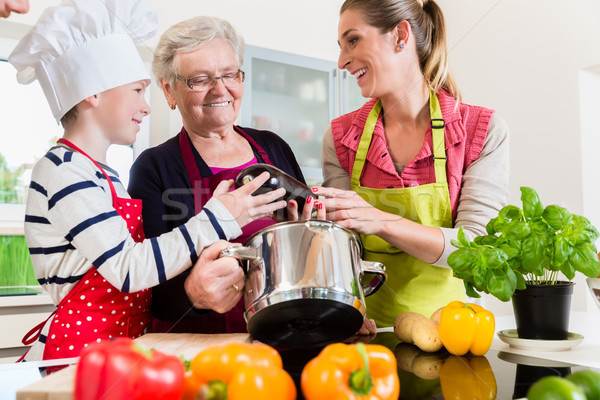 Granny, mum and son talking while cooking in kitchen Stock photo © Kzenon