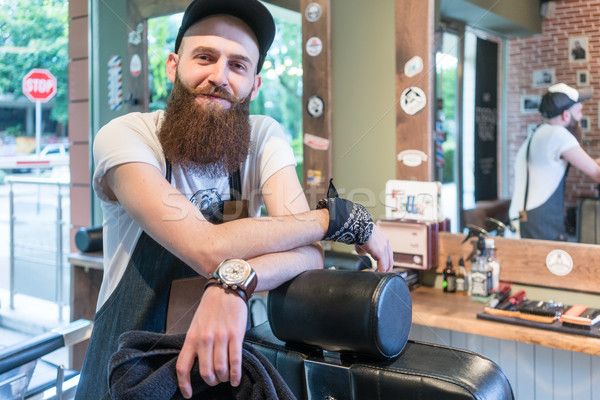 Portrait of a confident young barber smiling in a vintage beauty salon Stock photo © Kzenon