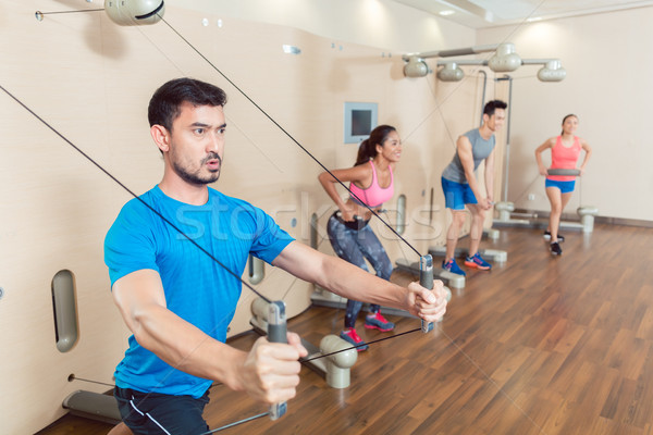 Determined young man exercising with resistance bands Stock photo © Kzenon