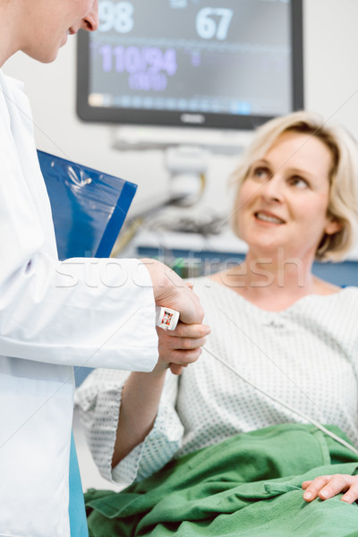 Doctor shaking hands of patient recovering after operation in hospital Stock photo © Kzenon
