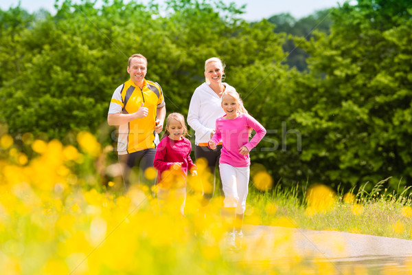 Family jogging in the meadow for fitness  Stock photo © Kzenon