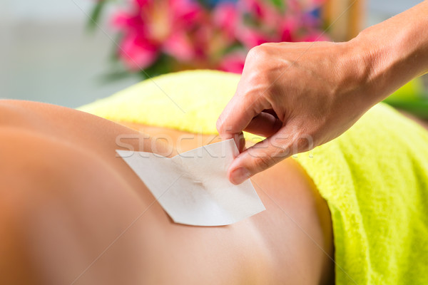 Man in Spa getting back waxed for hair removal Stock photo © Kzenon
